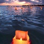 Honolulu, Hawaii: A lantern draped with a flower lei floats on the water